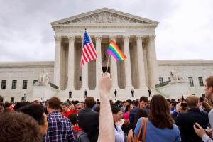 FILE - In this Friday June 26, 2015 file photo, a man holds a U.S. and a rainbow flag outside of the Supreme Court in Washington after the court legalized gay marriage nationwide. After the decision, religious conservatives are focusing on preserving their right to object. Their concerns are for the thousands of faith-based charities, colleges and hospitals that want to hire, fire, serve and set policy according to their religious beliefs, notably that gay relationships are morally wrong. (AP Photo/Jacquelyn Martin)